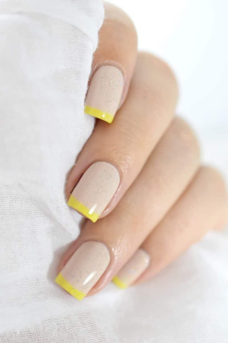 Le nail art minimaliste, c'est un peu notre nouveau chouchou. Elégant, tendance, raffiné et facile à réaliser à la maison, il s'impose comme le must-have de l'année. Découvrez 5 tutos faciles pour se mettre au nail art minimaliste! Pourquoi on craque sur le nail art minimaliste? La manucure minimaliste est un must-have du moment, notamment car c'est un style plus facile à porter qu'un nail art traditionnel, joli mais moins facile à assumer au bureau. Branché et facile à porter, le nail art minimaliste permet aussi (et peut-être surtout) de s'y essayer sans être une pro, puisqu'il ne nécessite que peu de matériel et surtout peu de talent artistique. Bonne nouvelle donc pour toutes celles qui rêvent d'ongles de stars mais qui n'ont pas les moyens ou l'envie de se rendre à un rendez-vous hebdomadaire chez une nail artist. Voici nos 5 manucures minimalistes préférées et le mode d'emploi pour réaliser la vôtre! Soin des mains: la base de tout nail art réussi Avant de se lancer dans un nail art, minimaliste ou non, on commence par faire un vrai soin des mains et des ongles. Pour cela, rien de compliqué: on commence par un bain de mains, et on réalise un petit gommage, en insistant sur le contour des ongles. Une fois les mains sèches, on applique une huile nourrissante sur les cuticules, qu'on masse et qu'on repousse ensuite. On insiste sur cette étape: il est important d'avoir une belle ligne de cuticule pour faire de jolis nail arts ensuite. Une fois les cuticules soignées, on se masse les mains avec une crème hydratante et on patiente jusqu'à son absorption. Une fois que votre crème a bien pénétré votre peau, imbibez un coton d'un peu de dissolvant et nettoyez vos ongles: le vernis sera plus facile à appliquer et séchera plus vite. Enfin, déposez une couche de base protectrice sur vos ongles, laissez sécher et passez au nail art minimaliste de votre choix! Tuto #1: La French Manucure 2.0 La French Manucure, tout le monde connaît, et sa version classique est, n'ayons pas